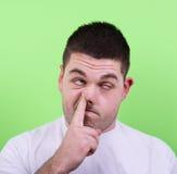 Retrato de un hombre joven con su finger en su nariz Fotografía de archivo libre de regalías