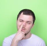 Retrato de un hombre joven con su finger en su nariz contra gree Fotos de archivo
