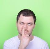 Retrato de un hombre joven con su finger en su nariz contra gree Imágenes de archivo libres de regalías