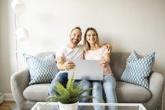 Retrato de un hombre joven con su novia en el ordenador portátil en casa interior fotografía de archivo