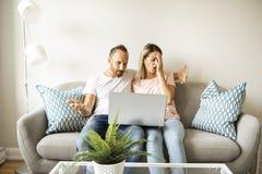 Retrato de un hombre joven con su novia en el ordenador portátil en casa interior foto de archivo libre de regalías