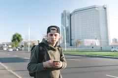 Retrato de un hombre joven con un teléfono en sus manos, escuchando la música en los auriculares y mirando en la cámara Foto de archivo libre de regalías
