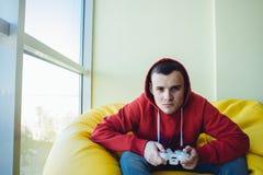 Retrato de un hombre joven con un gamepad en las manos de jugar a los videojuegos Videojuegos del concepto Fotografía de archivo libre de regalías