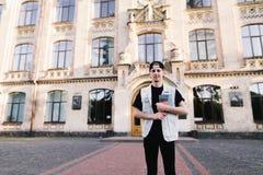 Retrato de un hombre joven con un ordenador portátil en su mano que se coloca en un campus de la universidad en el fondo de un ed Fotos de archivo