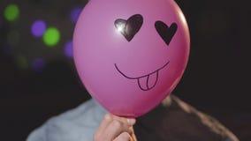 Retrato de un hombre joven confiado que pone el globo rosado con la cara divertida pintada en ella delante de su cabeza que mira  almacen de metraje de vídeo