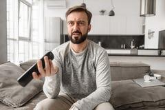 Retrato de un hombre joven decepcionado que sostiene la TV teledirigida imagen de archivo libre de regalías