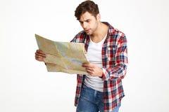 Retrato de un hombre joven desconcertado que mira el mapa del viaje Fotografía de archivo