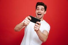 Retrato de un hombre joven emocionado en jugar blanco de la camiseta Imagen de archivo