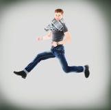 Retrato de un hombre joven emocionado que salta en aire contra Fotos de archivo libres de regalías