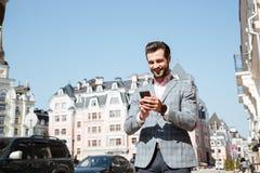 Retrato de un hombre joven en chaqueta usando el teléfono móvil Foto de archivo libre de regalías