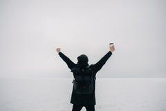 Retrato de un hombre joven en el negro que el invierno en el lago congelado siente libremente Imagen de archivo