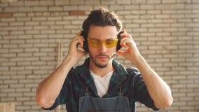 Retrato de un hombre joven en el taller de un carpintero en los vidrios protectores que miran la cámara Oncept del ¡de Ð de la pe almacen de metraje de vídeo