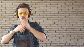 Retrato de un hombre joven en el taller de un carpintero en los vidrios protectores que miran la c?mara metrajes