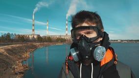 Retrato de un hombre joven en un respirador o una careta antigás En fondo el humo viene de los tubos de un hidroeléctrico almacen de metraje de vídeo