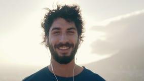Retrato de un hombre joven feliz con los auriculares en sus oídos en al aire libre metrajes