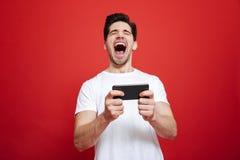 Retrato de un hombre joven feliz en la camiseta blanca que celebra Fotografía de archivo