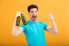 Retrato de un hombre joven feliz en la camiseta que sostiene la cerveza imágenes de archivo libres de regalías