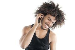 Retrato de un hombre joven feliz que escucha el teléfono móvil sobre el fondo blanco Fotografía de archivo