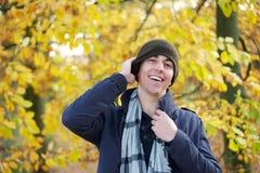 Retrato de un hombre joven feliz que ríe al aire libre con el sombrero Foto de archivo