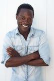 Retrato de un hombre joven feliz que ríe con los brazos cruzados Imagen de archivo libre de regalías