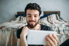 Retrato de un hombre joven feliz que relaja y que mira a una show televisivo en una tableta Imagen de archivo libre de regalías