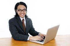 Retrato de un hombre joven feliz que usa la computadora portátil Fotografía de archivo libre de regalías
