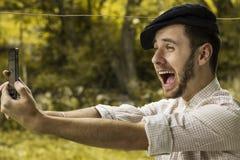 Retrato de un hombre joven hermoso con el casquillo que toma un teléfono del selfie imagenes de archivo