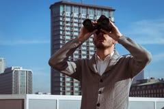 Retrato de un hombre joven hermoso que mira a través de los prismáticos Imagen de archivo libre de regalías
