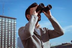 Retrato de un hombre joven hermoso que mira a través de los prismáticos Imágenes de archivo libres de regalías