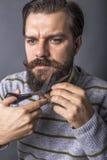 Retrato de un hombre joven que corta su barba con las tijeras imagen de archivo libre de regalías