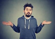 Retrato de un hombre joven que encoge los hombros que sienten desorientados foto de archivo libre de regalías