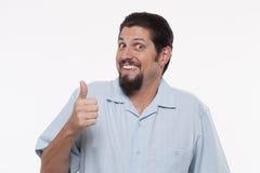 Retrato de un hombre joven que gesticula los pulgares para arriba contra blanco Fotos de archivo