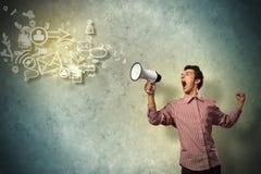 Retrato de un hombre joven que grita usando el megáfono Imagen de archivo