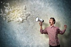 Retrato de un hombre joven que grita usando el megáfono Imagenes de archivo