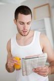 Retrato de un hombre joven que lee las noticias Imagenes de archivo