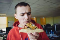 Retrato de un hombre joven que lleva a cabo una rebanada de pizza grande en un fondo de la oficina Fotografía de archivo libre de regalías