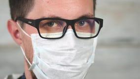 Retrato de un hombre joven que lleva vidrios y una máscara del trapo en su cara almacen de metraje de vídeo