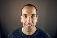 Retrato de un hombre joven que mira la cámara con la expresión y la sonrisa felices fotos de archivo libres de regalías