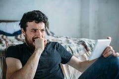 Retrato de un hombre joven que relaja y que mira a una show televisivo en una tableta imágenes de archivo libres de regalías