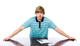Retrato de un hombre joven que se sienta detrás de un escritorio. Fotos de archivo libres de regalías