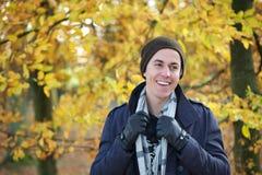 Retrato de un hombre joven que sonríe al aire libre en bufanda del sombrero de los guantes de la chaqueta Imagen de archivo