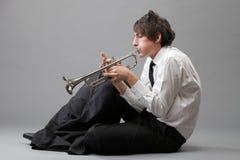 Retrato de un hombre joven que toca su trompeta Fotos de archivo