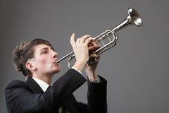 Retrato de un hombre joven que toca su trompeta Foto de archivo