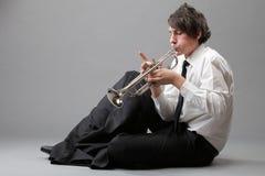 Retrato de un hombre joven que toca su trompeta Imágenes de archivo libres de regalías