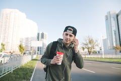 Retrato de un hombre joven sonriente con una taza de café en sus manos, escuchando la música en auriculares contra la perspectiva Fotografía de archivo libre de regalías