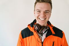 Retrato de un hombre joven sonriente en una chaqueta anaranjada y auriculares en un fondo ligero Foto de archivo libre de regalías