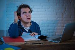 Retrato de un hombre joven subrayado y desesperado que estudia tarde en la noche en luz cambiante fotografía de archivo