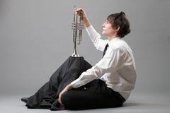 Retrato de un hombre joven y de su trompeta Foto de archivo