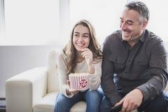 Retrato de un hombre joven y de una hija que ven la TV mientras que come las palomitas en el sofá Foto de archivo