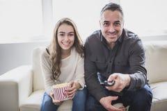 Retrato de un hombre joven y de una hija que ven la TV mientras que come las palomitas en el sofá Imagenes de archivo